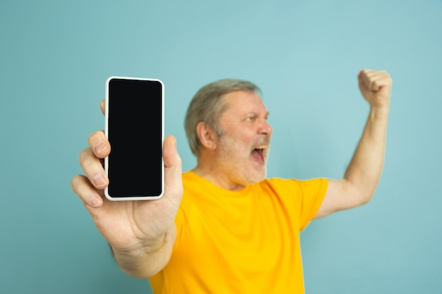 Caucasian man showing phone's blank screen on blue