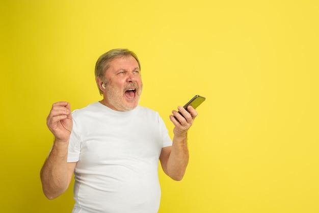 Кавказский мужчина поет с наушниками и смартфоном на желтом