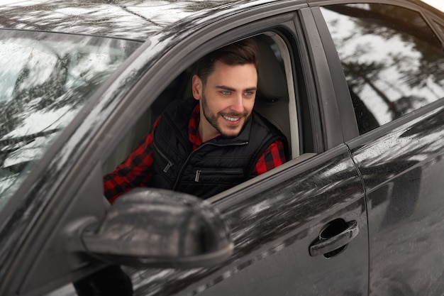 Кавказский мужчина сидит за рулем своей машины