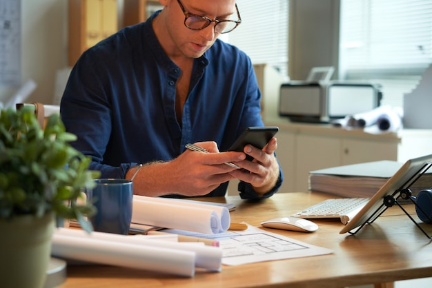 Caucasian man sitting at desk with rolled-up papers and plans and using smartphone