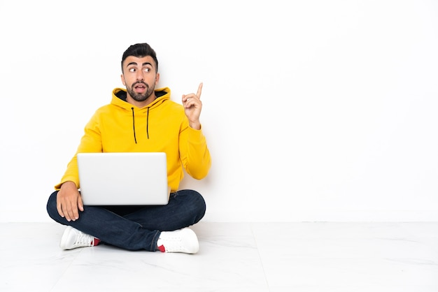 Caucasian man sitting on the floor with his laptop thinking an idea pointing the finger up