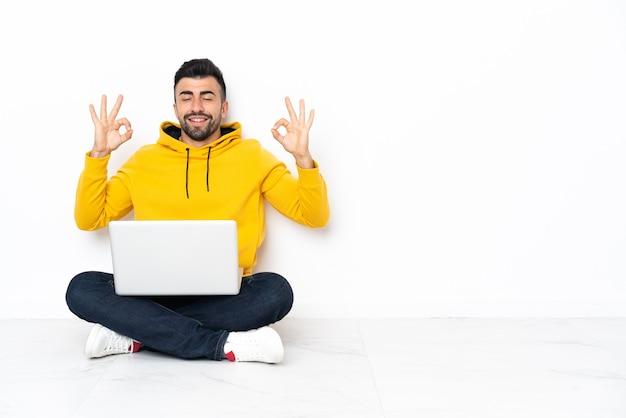 Кавказский мужчина сидит на полу со своим ноутбуком в позе дзен
