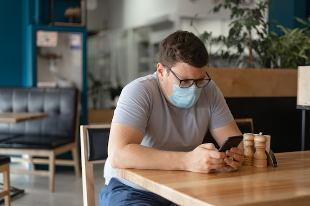 Caucasian man sitting in restaurant and using phone in medical face mask. new normal concept