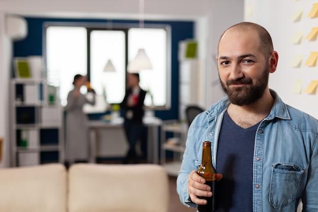 Кавказский человек улыбается и держит бутылку пива после работы в офисе. коллеги встречаются, чтобы развлечься, играя в игры, поедая алкоголь. праздничные напитки