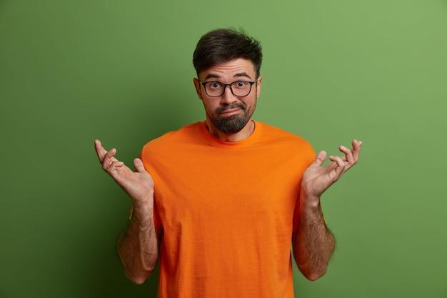 Кавказский мужчина развел руками в стороны, ничего не понимает, понятия не имеет, что произошло, недоумевает, чтобы ответить, одетый в оранжевую футболку, изолирован на зеленой стене. что случилось. нерешительный парень