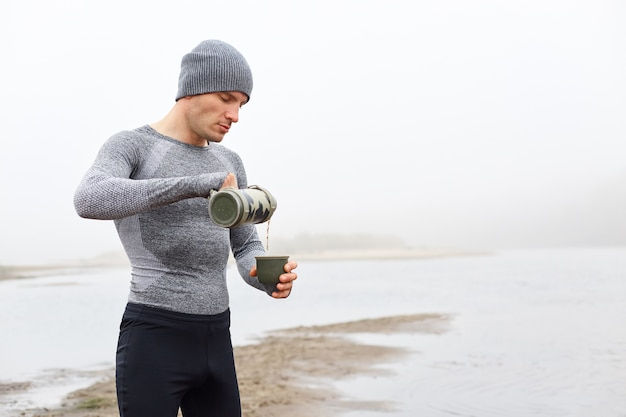 Caucasian man standing on bank of river in foggy day and drinking tea