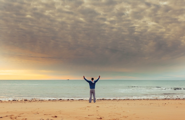Caucasian man standing at the ocean water on beach at sunset and raised hand
