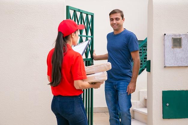 屋外に立って配達人に会う白人男性。赤い帽子とシャツを着たプロの宅配便業者が、小包や箱を徒歩で顧客に配達します。速達サービスとポストコンセプト