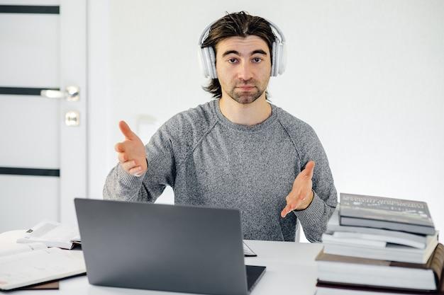 白人男性の学生教師の家庭教師は、ラップトップコンピューターでワイヤレスヘッドセットビデオ会議を着用し、ウェブカメラで話し、オンラインチャットで教え、距離ウェビナーオンライン教育の概念を学びます