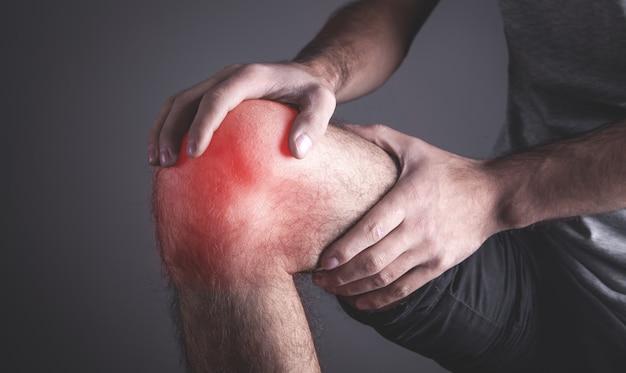 Кавказский мужчина страдает от боли в колене.