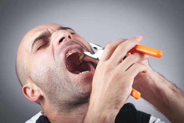 Caucasian man suffering from toothache holding pliers.