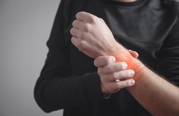 손목 통증으로 고통받는 백인 남자.