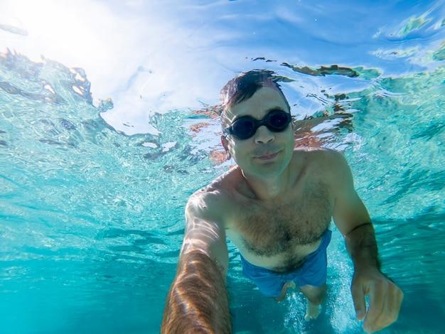 수영 고글 푸른 투명한 물에 물 속에서 수영하는 백인 남자