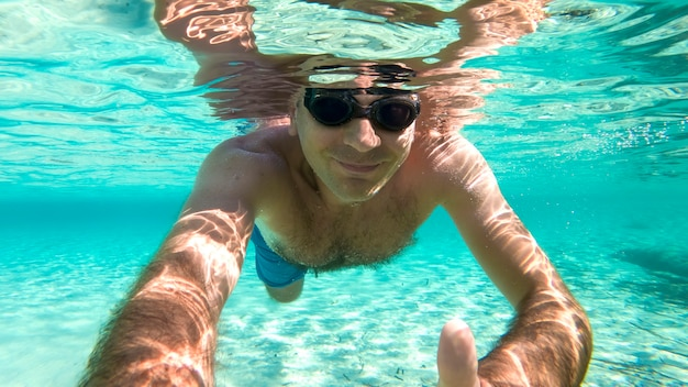 Caucasian man swimming under the water in swimming goggles  blue transparent water