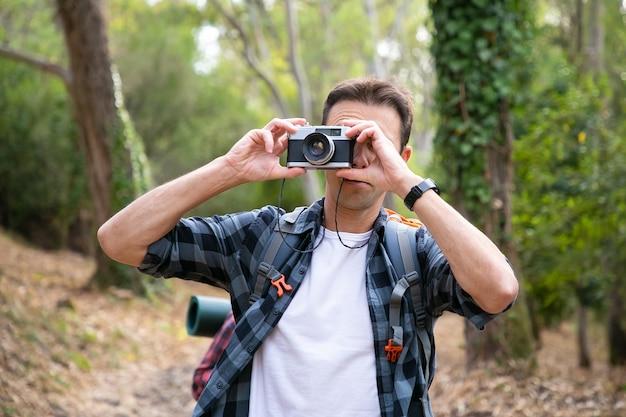カメラで自然の写真を撮り、林道に立っている白人男性。森の中を歩いたりハイキングしたりする若い男性旅行者。観光、冒険、夏休みのコンセプト