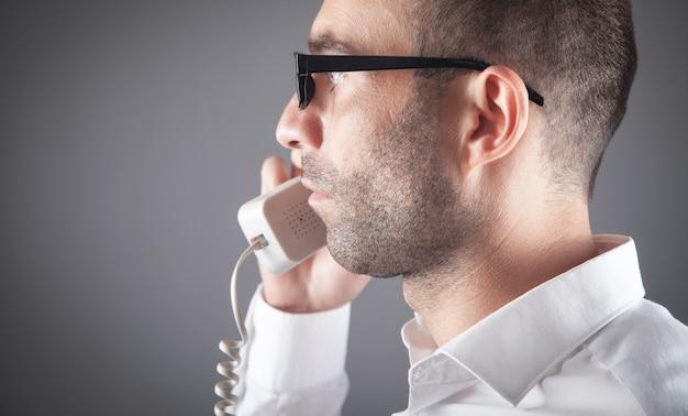 Caucasian man talking on office telephone.