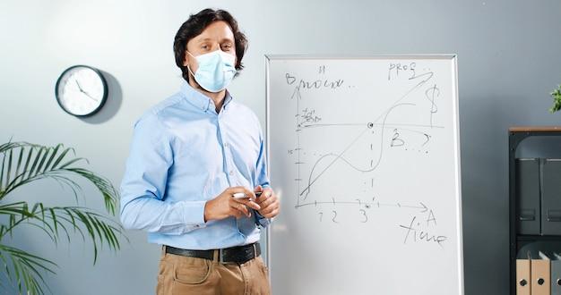 Кавказский мужчина-учитель в медицинской маске и очках стоит за доской в классе и рассказывает классу законы физики или геометрии. концепция коронавируса. школа во время covid-19. учебная лекция.