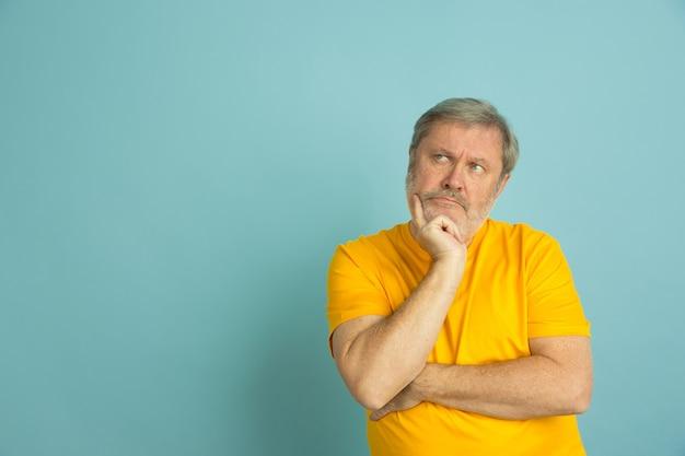 Кавказский мужчина задумчивый, глядя на сторону, изолированную на синем