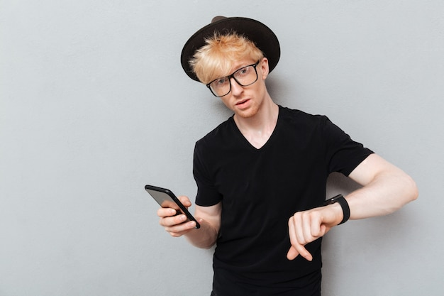 Caucasian man using his watch and mobile phone.