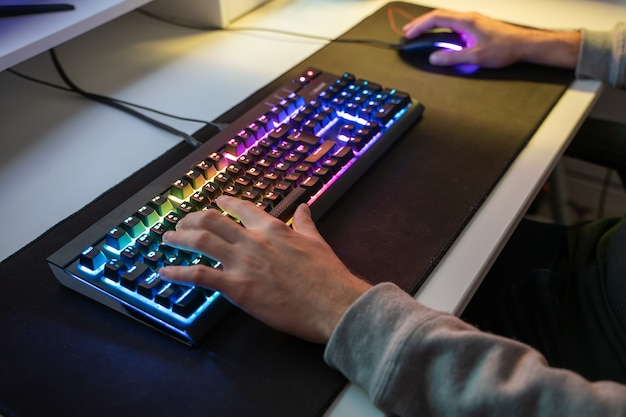 Caucasian man using the keyboard of his gamer computer with led lights and playing games