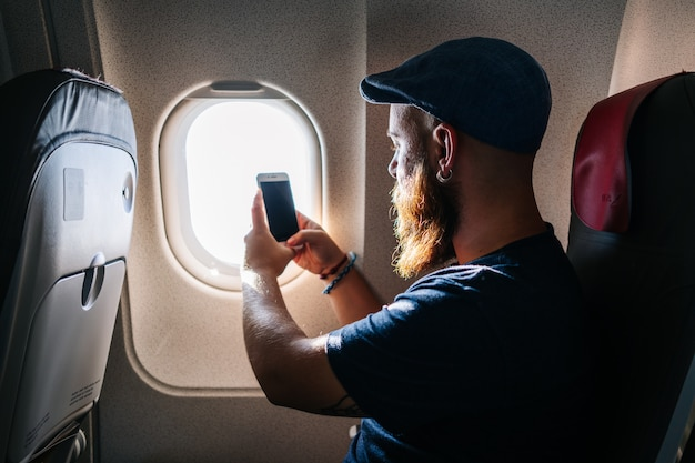 Caucasian man using phone into the airplane