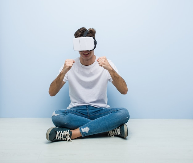 Caucasian man using a virtual reality glasses sitting on the floor