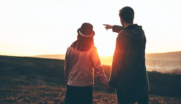 フィールドで彼のガールフレンドと手をつないで歩いている白人男性は完璧な夕日を指しています