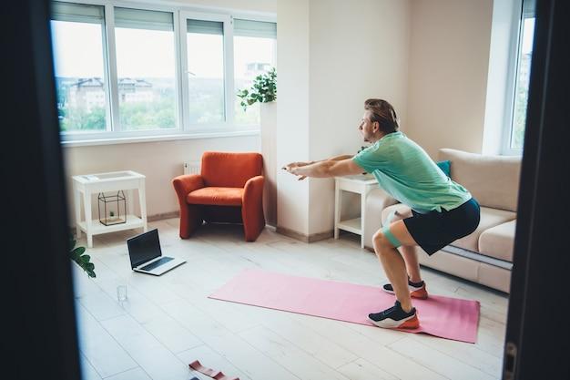Кавказский мужчина разминается дома во время удаленных уроков фитнеса с помощью ноутбука