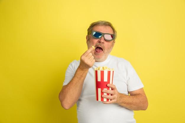 Uomo caucasico che guarda il cinema con popcorn e occhiali 3d su colore giallo