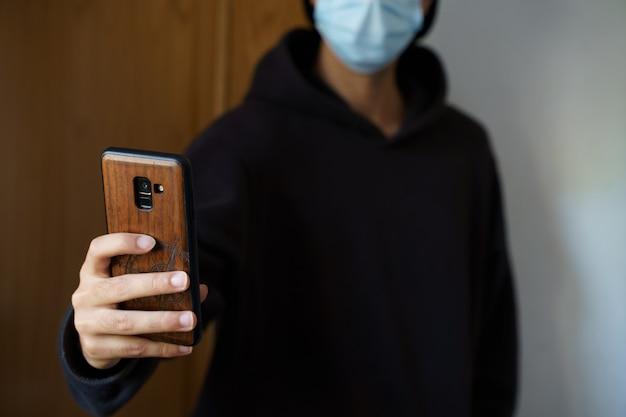 サージカルマスクを着用した白人男性がスマートフォンで自分撮りをしています。パルマデマヨルカ、スペイン