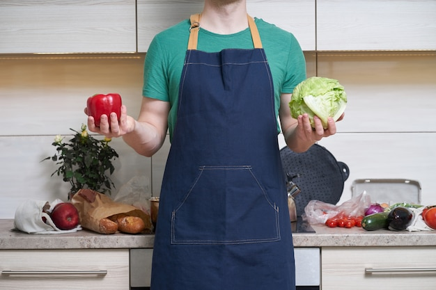Caucasian man wearing apron stands in kitchen and holding vegitables in hands