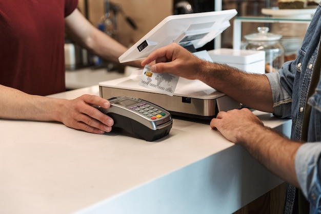Caucasian man wearing denim shirt paying debit card in cafe while waiter holding payment terminal