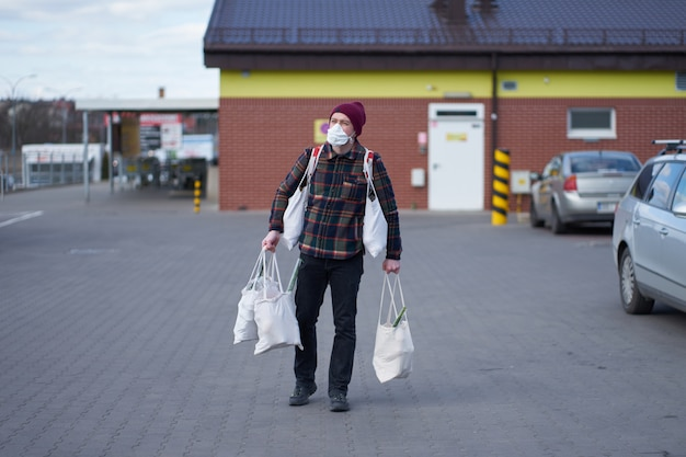 Caucasian man wearing medical mask carryin bags with food after shopping during outbreak