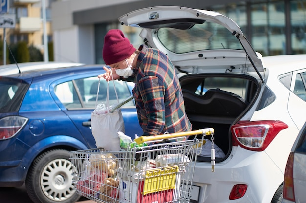 Caucasian man wearing medical mask packs bags with food from cart into car after shopping during outbreak