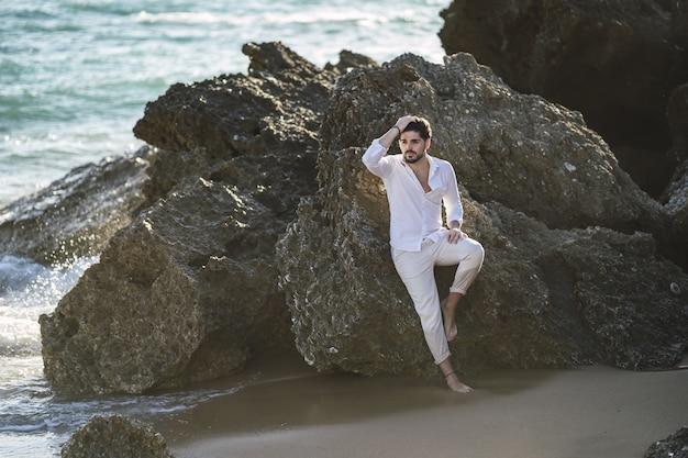 Uomo caucasico che indossa abiti bianchi seduto sulla pietra sulla spiaggia