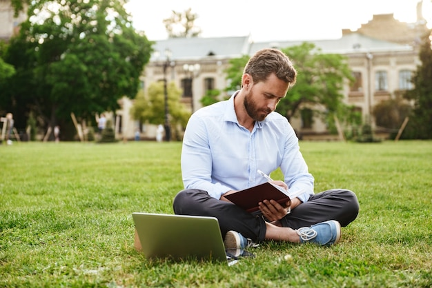 Caucasian man wearing white shirt, sitting on grass in park with legs crossed and writing down notes in notebook while working on laptop