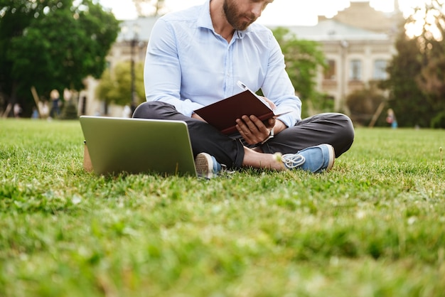 Caucasian man wearing white shirt, writing down notes in notebook while sitting on grass in park with legs crossed and working on laptop