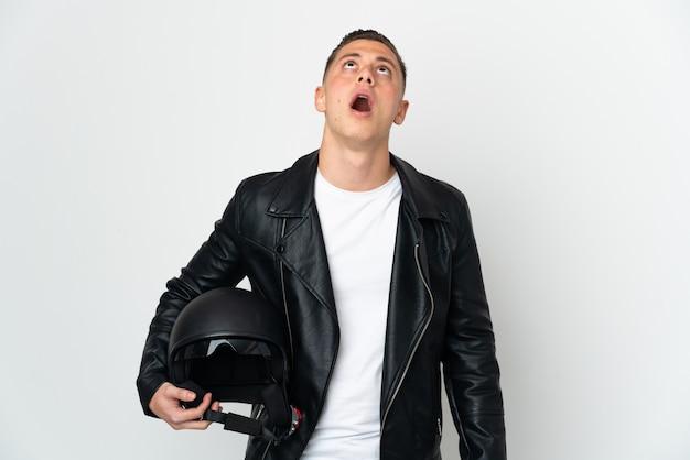 고립 된 오토바이 헬멧을 가진 백인 남자를 찾고 놀란 표정으로