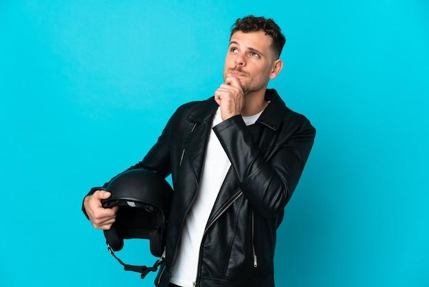 블루에 고립 된 오토바이 헬멧을 가진 백인 남자를 찾고