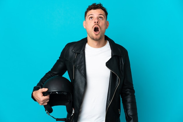 파란색을 찾고 놀란 표정으로 고립 된 오토바이 헬멧을 가진 백인 남자
