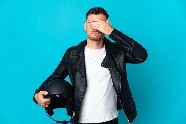손으로 눈을 덮고 파란색 벽에 고립 된 오토바이 헬멧 백인 남자. 뭔가보고 싶지 않아
