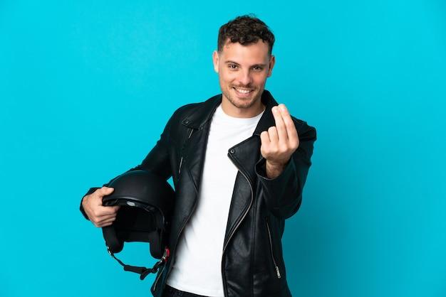 Кавказский мужчина в мотоциклетном шлеме изолирован на синей стене, делая денежный жест