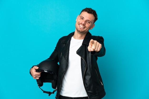 幸せな表情で正面を向いている青い壁に分離されたオートバイのヘルメットを持つ白人男性