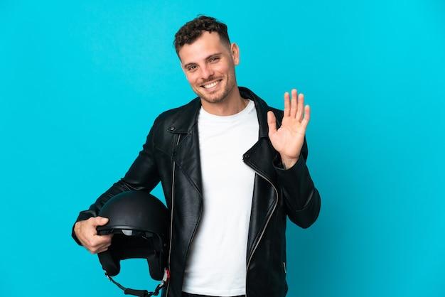 幸せな表情で手で敬礼青い壁に分離されたオートバイのヘルメットを持つ白人男性