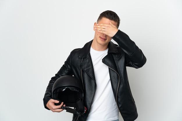 손으로 눈을 덮고 흰색 배경에 고립 된 오토바이 헬멧 백인 남자. 뭔가보고 싶지 않아