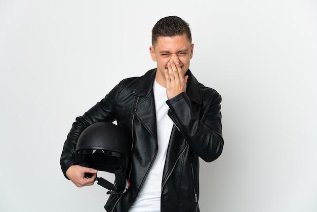 Кавказский мужчина в мотоциклетном шлеме на белом фоне счастлив и улыбается, прикрывая рот рукой