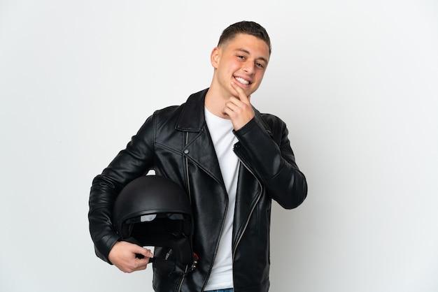 Кавказский человек с мотоциклетным шлемом на белом фоне счастлив и улыбается