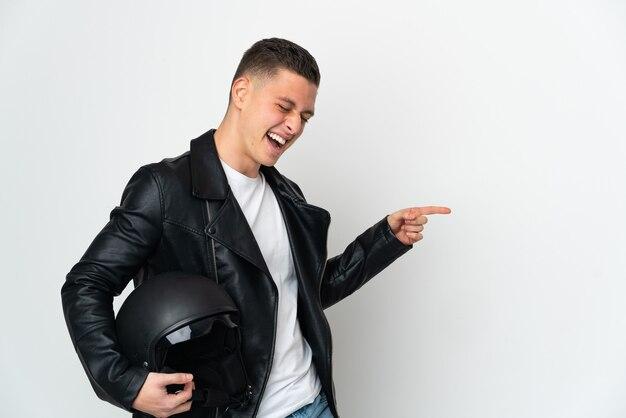 측면에 손가락을 가리키고 제품을 제시하는 흰색 배경에 고립 된 오토바이 헬멧 백인 남자