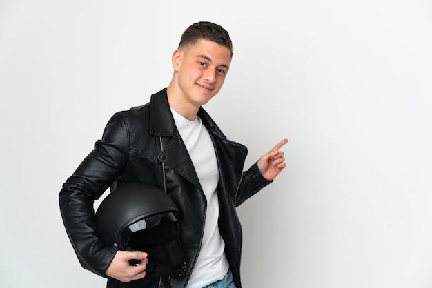 横に指を指している白い背景で隔離のオートバイのヘルメットを持つ白人男性