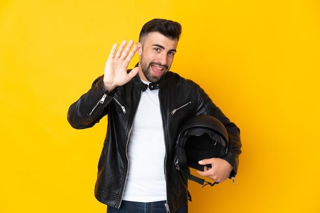 幸せな表情で手で敬礼する孤立した黄色の壁にオートバイのヘルメットを持つ白人男性
